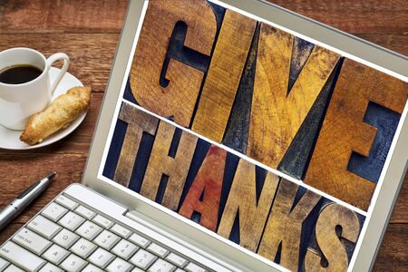 thanks: Give thanks - Thanksgiving concept - text in vintage letterpress printing blocks on a laptop screen with a cup of coffee Stock Photo