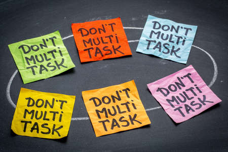 multitask: do not multitask sticky note abstract against blackboard - efficiency and productivity advice or reminder Stock Photo