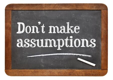 assumptions: Do not make assumptions advice or reminder   - text in white chalk on a vintage slate blackboard
