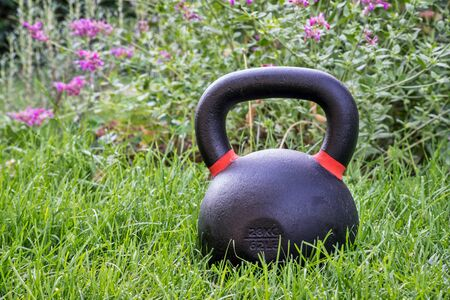 outdoor fitness: iron kettlebell on green grass in a backyard - outdoor fitness concept