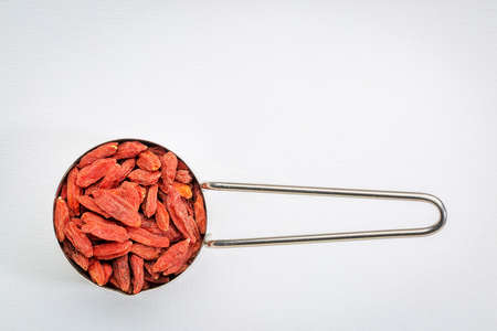 metal measuring scoop of dried goji berries against white art canvas with a copy space