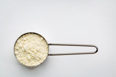 measuring metal scoop of whey protein powder against rustic white art canvas with a copy space 스톡 사진