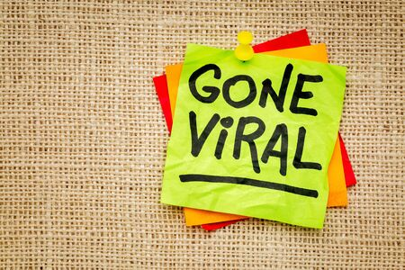 Gone viral - handwriting on a sticky note against burlap canvas 스톡 사진