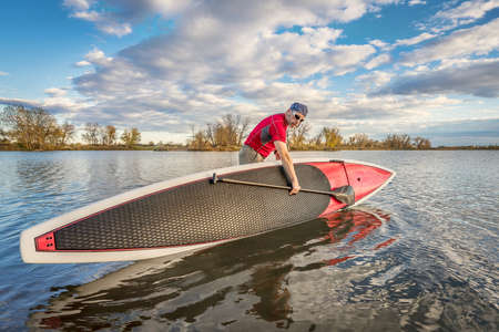 senior male launching  his 14 feet long expedition stand up paddleboard on a lake in Colorado, fall scenery 스톡 사진