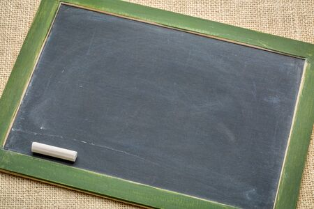 blank spaces: blank vintage slate blackboard with a white chalk against burlap canvas