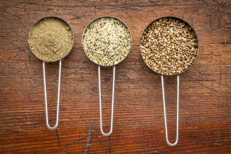 abstract food: hemp seeds, hearts and protein powder in metal measuring scoops against grunge wood