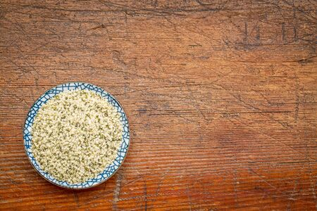 shelled hemp seeds (hearts) in a round ceramic bowl against rustic, grunge wood