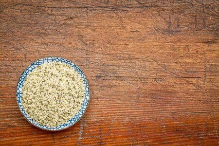 hemp hemp seed: shelled hemp seeds (hearts) in a round ceramic bowl against rustic, grunge wood