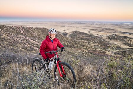 fort collins: senior male with a mountain bike in a rolling prairie at dusk, Soapstone Prairie Natural Area near Fort Collins, Colorado