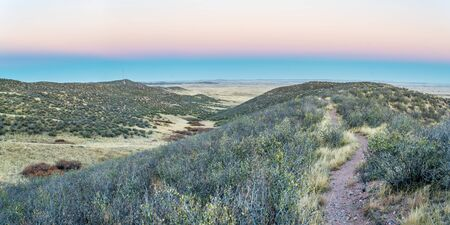 soapstone: singletrack bike trail at dusk light in rolling prairie at foothills of Rocky Mountains in Colorado - Soapstone Open Space near Fort Collins Stock Photo