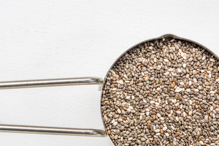 chia seeds in metal measuring coop against white art canvas with a copy space 스톡 사진