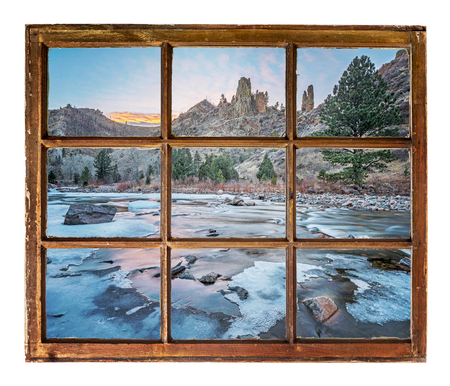 travel concept  or a greeting card from Colorado - Poudre River in winter as seen  through vintage, grunge, sash window with dirty glass Stock Photo