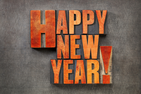 Happy New Year! - text in vintage letterpress wood type blocks stained by red ink on a grunge metal background 스톡 사진