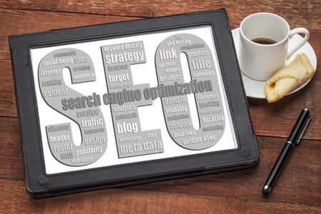 keywords link: SEO - search engine optimization word cloud  on a digital tablet with a cup of coffee