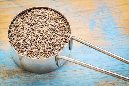 chia seeds in a metal measuring coop against white wood background