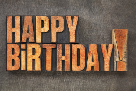 Happy Birthday! -  text in vintage letterpress wood type blocks stained by red ink  on a grunge metal background
