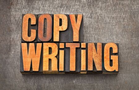 copywriting: copywriting word - vintage letterpress wood type stained by red ink on a grunge metal background Stock Photo
