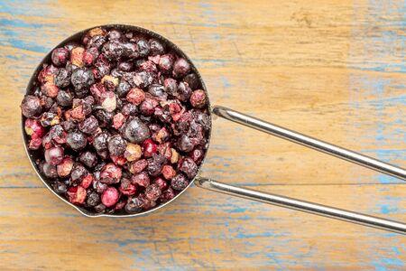 superfruit: freeze dried elderberries in a metal measuring scoop against grained wood