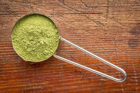 moringa leaf powder in a metal measuring scoop against rustic wood