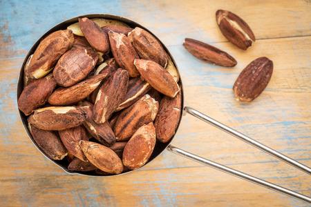 pili: metal measuring scoop of roasted pili nuts against wood background
