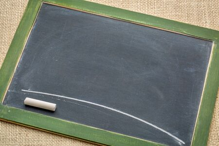 blank vintage slate blackboard with a white chalk line against burlap canvas 스톡 사진