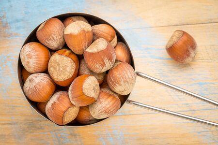 metal measuring scoop of hazelnuts (in shells) against grunge wood table