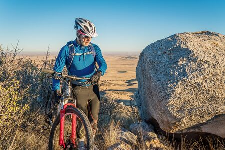 senior male with a mountain bike in Colorado foothills, Soapstone Prairie Natural Area near Fort Collins 스톡 사진