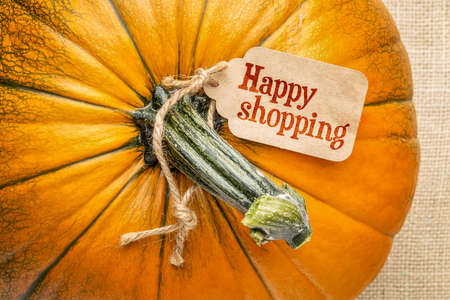 A pumpkin against burlap canvas with a happy shopping  price tag 스톡 사진