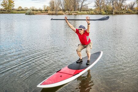 paddler: senior male paddler stretching and warming up on a paddleboard before paddling workout on a lake in Colorado
