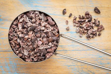 Raw cacao nibs in a metal measuring scoop against wooden background