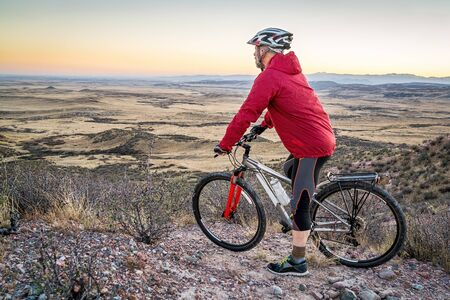 senior male with a mountain contemplating  dusk over rolling prairie,  Soapstone Prairie Natural Area near Fort Collins, Colorado Stock Photo