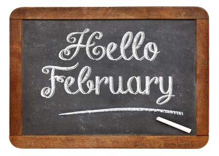 february: Hello February sign  - white chalk text on an isolated  vintage slate blackboard