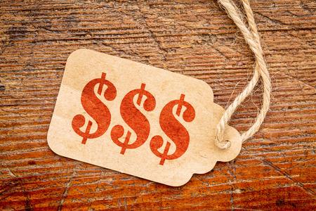 signo pesos: el triple signo de dólar - el texto de la plantilla roja en un precio de papel contra la madera rústica Foto de archivo