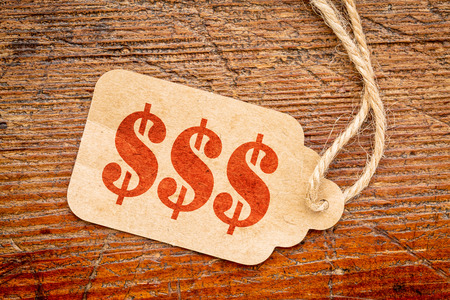 triple dollar sign - red stencil text on a paper price tag against rustic wood Stockfoto