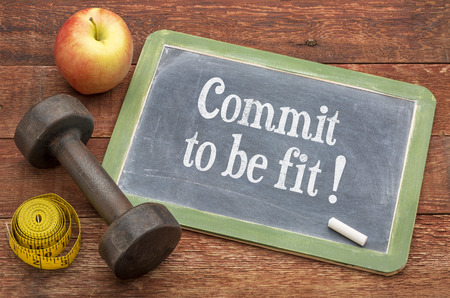 Commit to be fit concept -  slate blackboard sign against weathered red painted barn wood with a dumbbell, apple and tape measure Stockfoto