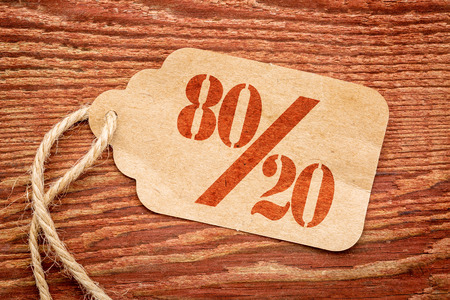 Pareto principle or eighty-twenty rule represented on a paper price tag against rustic wood