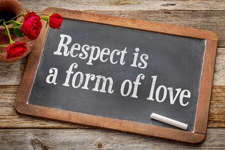 respetar: El respeto es una forma de amor - texto blanco de la tiza en una pizarra pizarra de la vendimia con las rosas rojas contra la madera rústica