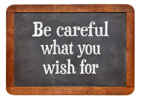 Be careful what you wish for warning - text  on a vintage slate blackboard