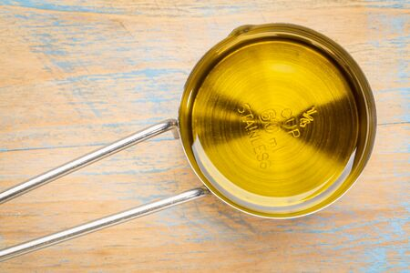 cooking oil: olive oil in a metal measuring cup against painted wood