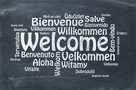 Welcome in different languages - a word cloud in white chalk text on a vintage slate blackboard