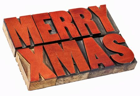 wood sign: Merry Christmas  (Xmas) - isolated  word abstract in vintage letterpress wood type stained by red ink Stock Photo
