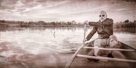 paddler: senior paddler enjoying paddling a canoe on a calm lake at sunset, a grunge texture finish in sepia tone