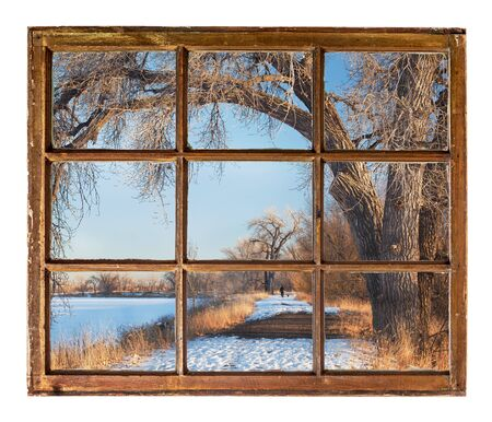 winter park scene with a trail, frozen lakes and old cottonwood trees as seen from a sash window of old cabin