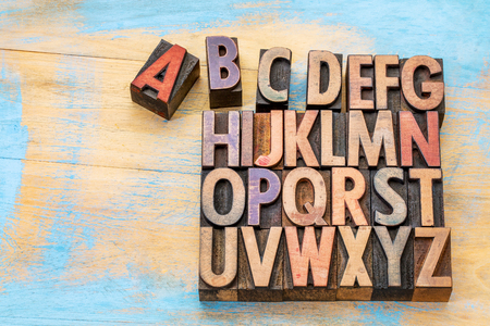 letter b: alphabet concept in vintage letterpress wood type stained by color inks against painted wood with a copy space