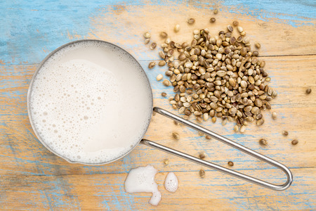 hemp milk in measuring cup with seeds against wooden background