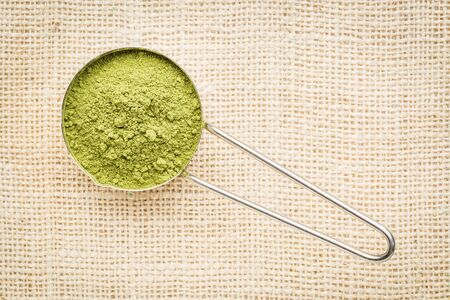oleifera: moringa leaf powder in a metal measuring scoop against burlap canvas Stock Photo