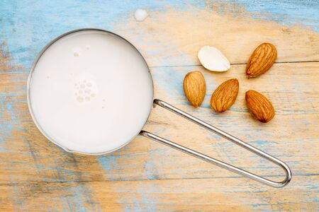 almond: almond milk in measuring cup with almond nuts against wooden background Stock Photo