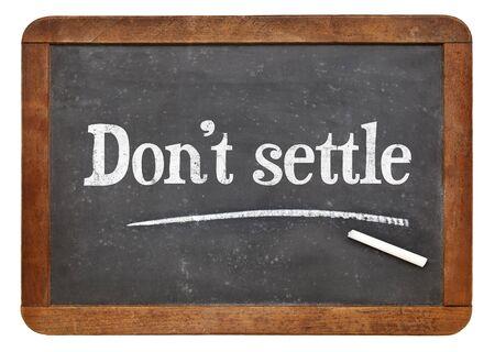 settle: Do not settle - motivational advice in white chalk on a vintage slate blackboard Stock Photo