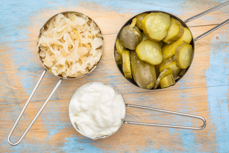 probiotic: sauerkraut, cucumber pickles and yogurt - popular probiotic fermented food - three measuring cups against rustic wood Stock Photo