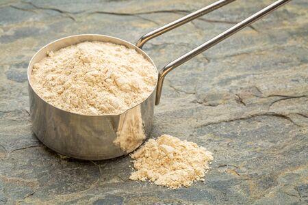 maca: maca root powder on a metal measuring scoop against slate stone
